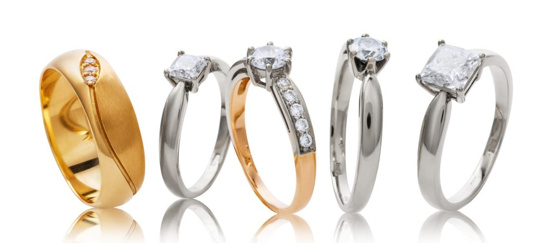 Various wedding gold rings with diamonds isolated on white background
